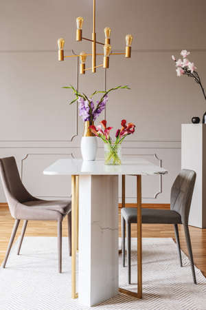 Flowers on table in grey dining room interior with gold lamp and chairs on carpet. Real photo