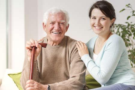 Smiling woman hugging happy senior man with walking stick during family meeting