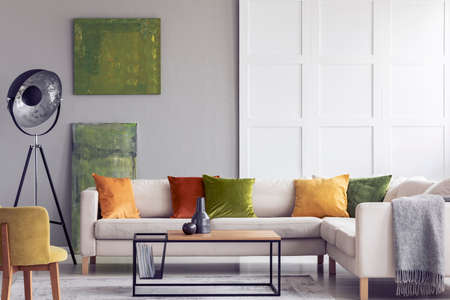 Yellow and green pillows on white settee in living room interior with paintings and lamp. Real photo