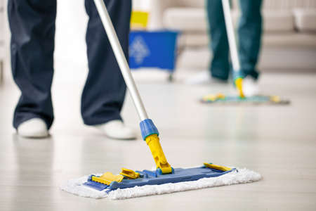 Photo pour Close-up on mop on the floor holding by cleaning expert while purifying interior - image libre de droit