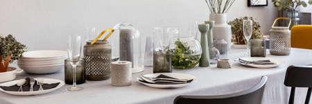 Foto de Panorama of grey table with wine glasses, candles and tableware in dining room interior. Real photo - Imagen libre de derechos