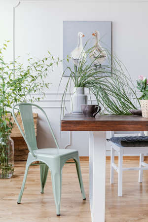 Photo for Vertical view of mint green chair next to wooden table with vase with green plant in it and big coffee mug, rustic oil painting n the wall - Royalty Free Image