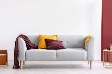 Photo pour Burgundy pillow and blanket and yellow pillow and blanket on stylish grey couch in elegant living room interior with copy space on the white empty wall - image libre de droit
