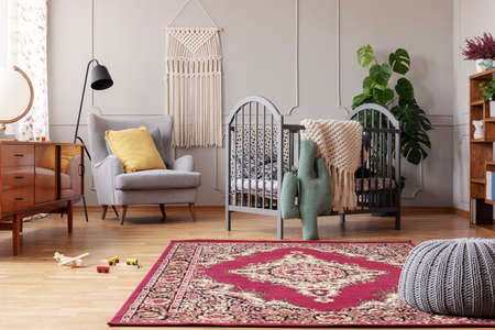 Photo for Rustic rug in stylish baby bedroom with grey and vintage furniture, real photo with copy space - Royalty Free Image
