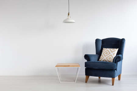 Photo pour White simple lamp above wooden coffee table in stylish minimal interior with dark blue armchair with patterned pillow, real photo with copy space - image libre de droit