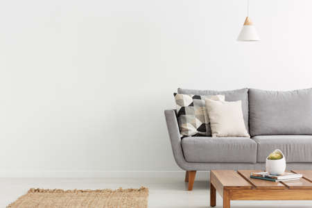 Wooden table in front of grey sofa with cushions in white flat interior with copy space. Real photo