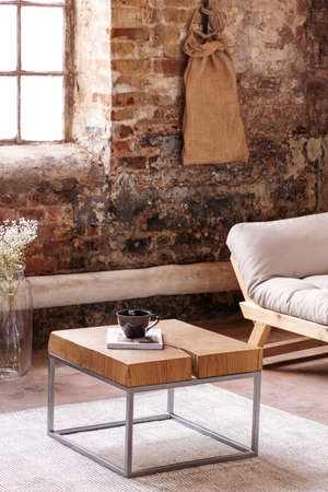 Wooden table on carpet between flowers and couch in flat interior with red brick wall. Real photo