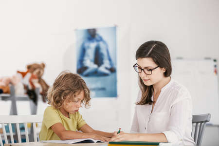 Friendly teacher doing homework with young boy in the classroom