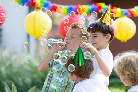 Foto de Happy boys with colorful hats making soap bubbles during outdoor birthday party - Imagen libre de derechos