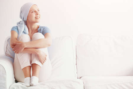 Photo pour Bright photo of happy pretty girl suffering from kidney cancer, wearing blue headscarf and siting on the couch at hospice after chemotherapy - image libre de droit