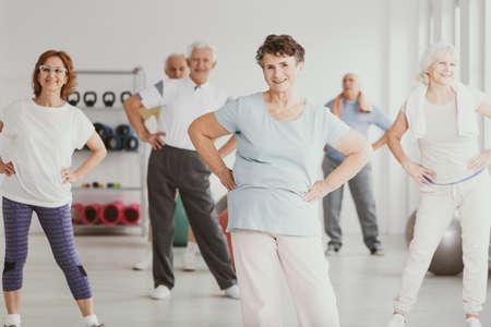 Foto de Happy senior woman holding hips during gymnastic classes for elderly people - Imagen libre de derechos