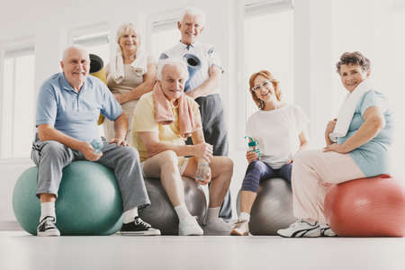 Low angle on smiling active elderly people on balls after physical classes in sport club