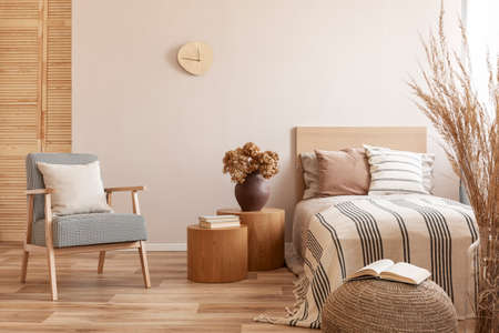 Photo for Stylish retro armchair with white pillow next to two round wooden tables with books and vase with flowers in beige bedroom interior - Royalty Free Image
