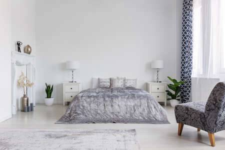Photo pour Trendy armchair in bedroom designed in new york style, real photo with copy space - image libre de droit