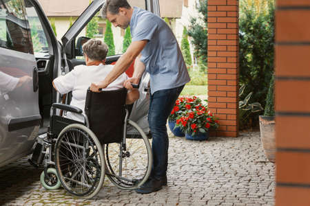 Photo pour Helpful male nurse with senior lady on wheelchair helping her get in to the car - image libre de droit