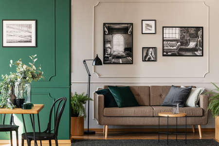 Photo pour Black and white photos on grey wall of chic living and dining room interior with brown couch and wooden table - image libre de droit