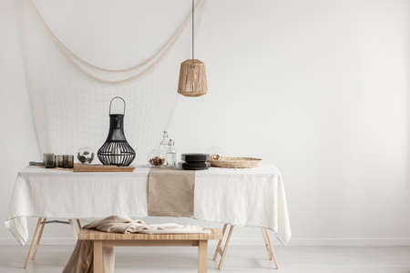 Photo for Rattan lamp above dining table with wicker plateau and black glass plates and elegant metal lantern, copy space on empty white wall - Royalty Free Image
