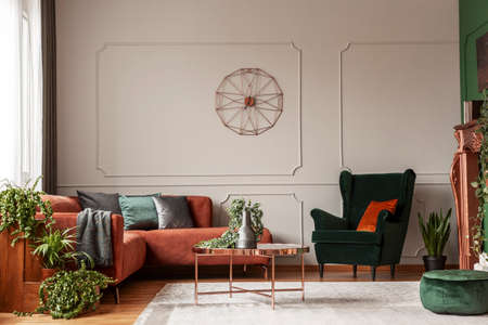 Photo pour Velvet emerald green armchair with orange pillow next to corner sofa and coffee table - image libre de droit