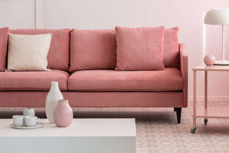 Photo pour Pastel pink and white vases and coffee mugs on small table in pink living room interior with comfortable sofa - image libre de droit