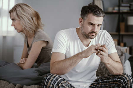 Photo pour Man in pajamas sitting in bed and taking off his wedding ring after his wife announced that she wanted to get a divorce - image libre de droit