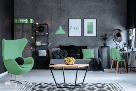 Photo for Green armchair next to wooden table in dark living room interior with posters above couch. Real photo - Royalty Free Image
