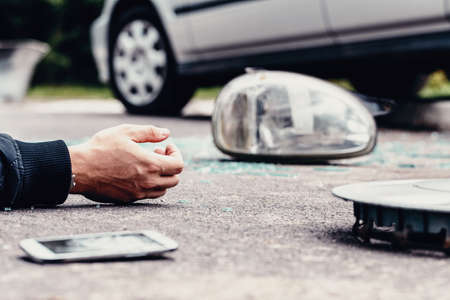 Photo pour Human's hand on the ground next to broke car mirror and mobile phone after a crash - image libre de droit