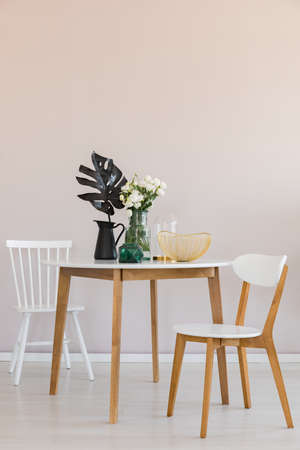 Photo for Stylish dining room with round table and elegant chairs, copy space on the empty wall - Royalty Free Image