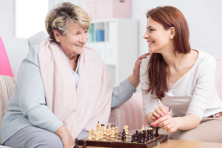 Photo for Happy granddaughter playing chess with her grandmother in senior care center - Royalty Free Image