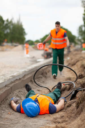 Photo pour Accident during road construction, injured worker lying on the ground - image libre de droit