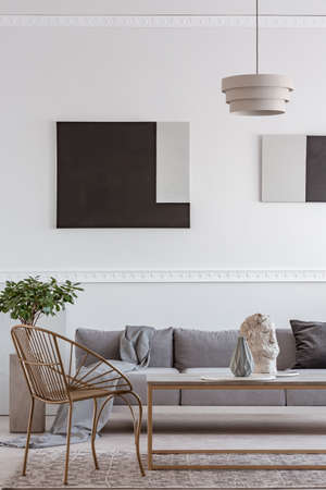 Photo pour Stylish golden chair next to coffee table with vase in front of grey couch - image libre de droit