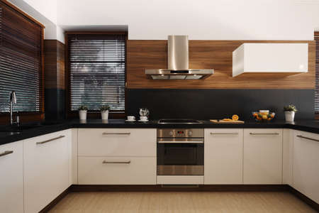 Photo pour Elegant white and black kitchen with wooden accents and silver oven and sink - image libre de droit