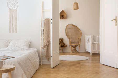 Photo pour Scandinavian bedroom with white bedding on the bed and door open to stylish nursery with white wooden crib and wicker peacock chair, real photo - image libre de droit