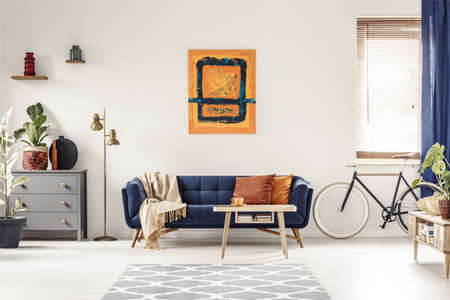 Foto de Yellow and blue painting hanging on white wall in bright living room interior with grey cupboard, gold lamp, sofa with blanket and pillows, and bike standing under window with blinds - Imagen libre de derechos