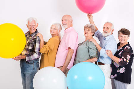 Older married couples dancing in a line at the party