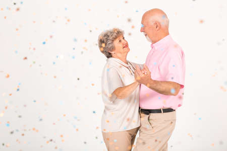 Older married couple dancing together at the party