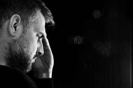 Foto de Copy space on black background next to face of worried man with problem - Imagen libre de derechos