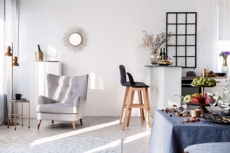 Photo for Trendy grey armchair next to two black wooden bar stools in fashionable kitchen and dining room interior - Royalty Free Image