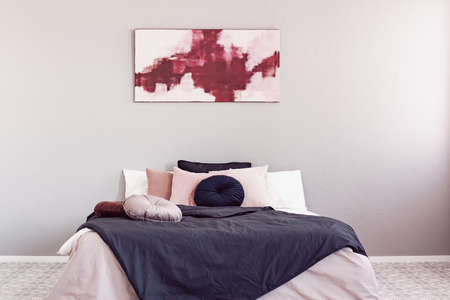 Photo for Abstract amaranth and pastel pink painting above king size bed with pink and black bedding - Royalty Free Image