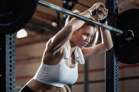 Photo for Tired pretty girl resting after weight lifting at fitness center - Royalty Free Image