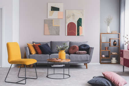 Foto de Real photo of a yellow chair and gray couch with pillows in a modern living room interior - Imagen libre de derechos
