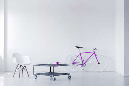 Photo for Purple bike, chair and metal coffee table in a minimalistic room interior. Real photo - Royalty Free Image