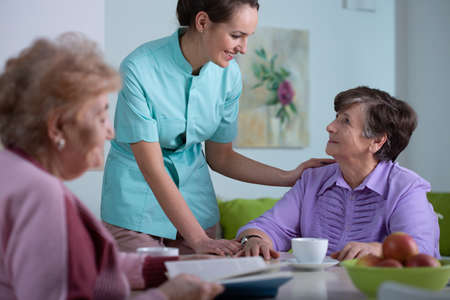 Photo for Senior patient of professional nursing home and helpful young nurse - Royalty Free Image