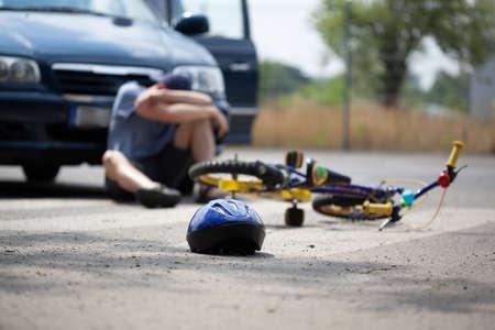 Photo pour Despair driver sitting next to car after accident with bike - image libre de droit