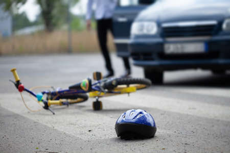 Photo pour Helmet and bike on the steet after accident with car - image libre de droit