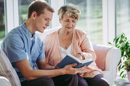 Photo pour Senior woman and her male nurse reading a book together - image libre de droit