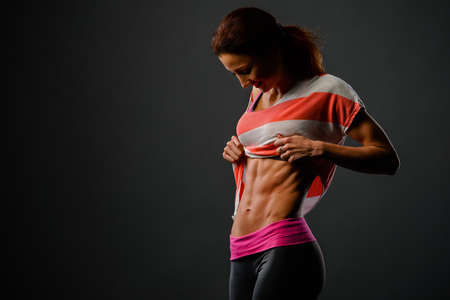 Photo of sporty girl in studio looking at her chest and happy with her results
