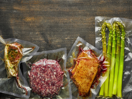 Foto für Meat and asparagus vacuum sealed ready for sous vide cooking on wooden table, from above - Lizenzfreies Bild