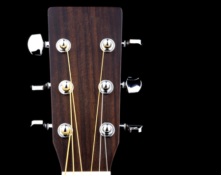 Acoustic guitar peg head isolated against a black background