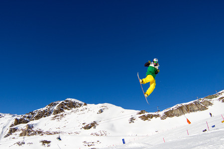 Snowboarder in colorful clothing performing a bold move in snow park. Trademarks have been r