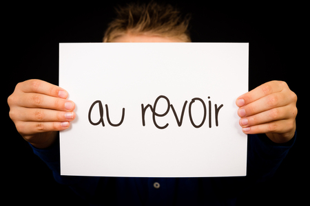 Studio shot of child holding a sign with French word Au Revoir - Goodbye